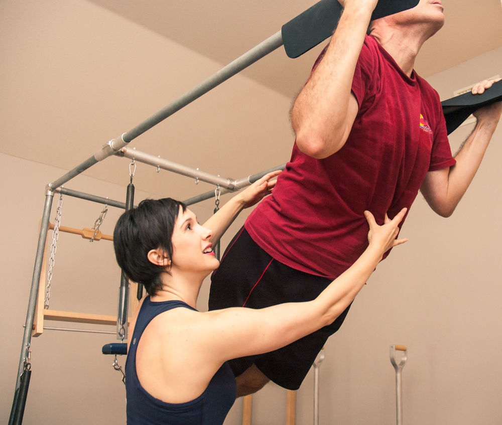 Collette of Collette Pilates guiding a client through proper form for maximum benefit.