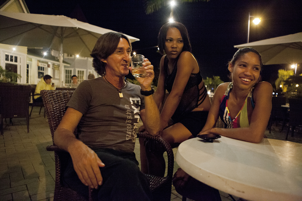 """Bereniseand Chabeli have drinkswith a client at a restaurant in the tourist waterfront.The Canadian tourist is a regular client for Chabeli and he believes that she is 21, not 15. When asked why he likes come to Samaná for the winter, he said, """"This place is a paradise for men. These Dominican women just love to have sex."""""""