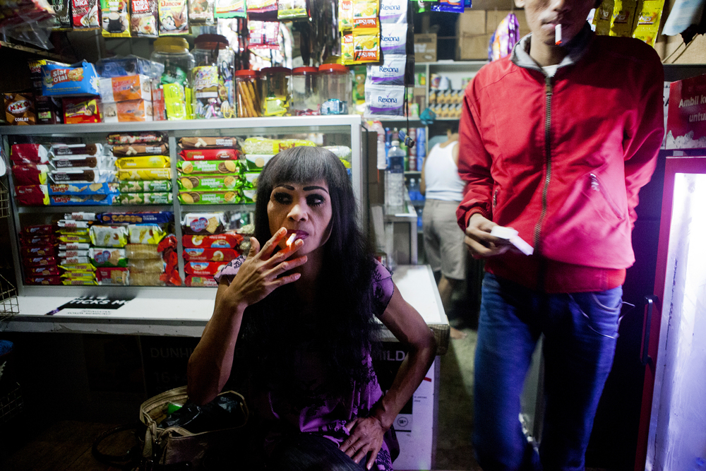 "Miska smokes a cigarette at a corner store across from the railroad tracks. The specific section of railroad tracks she works on is for waria prostitutes only. They work to keep out any ""real women"" prositutes."