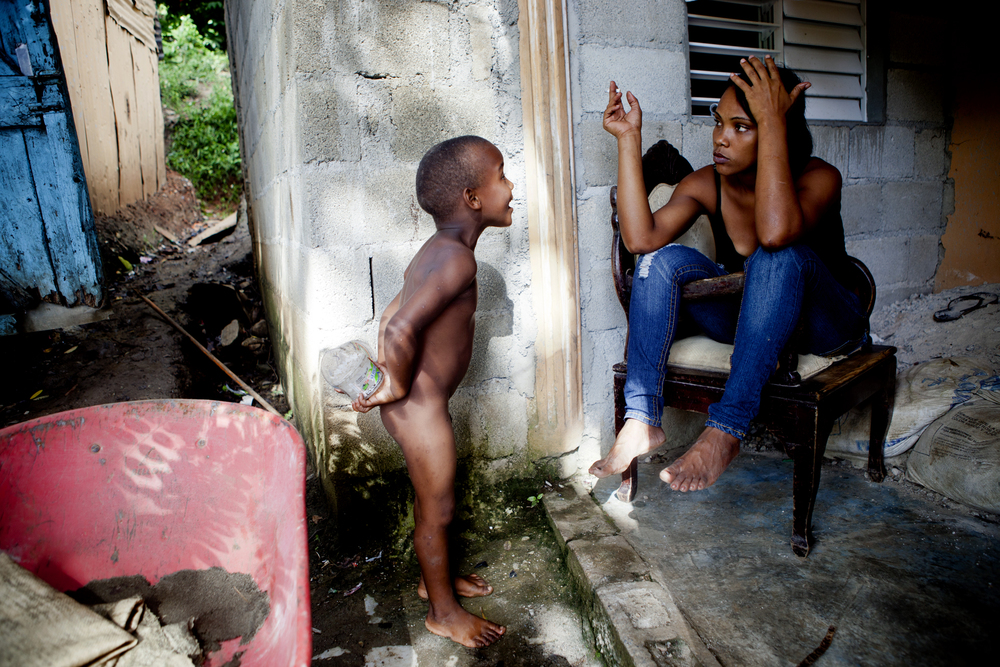 Berenise smokes a cigarette outside of her home while her youngest son throws a fit.