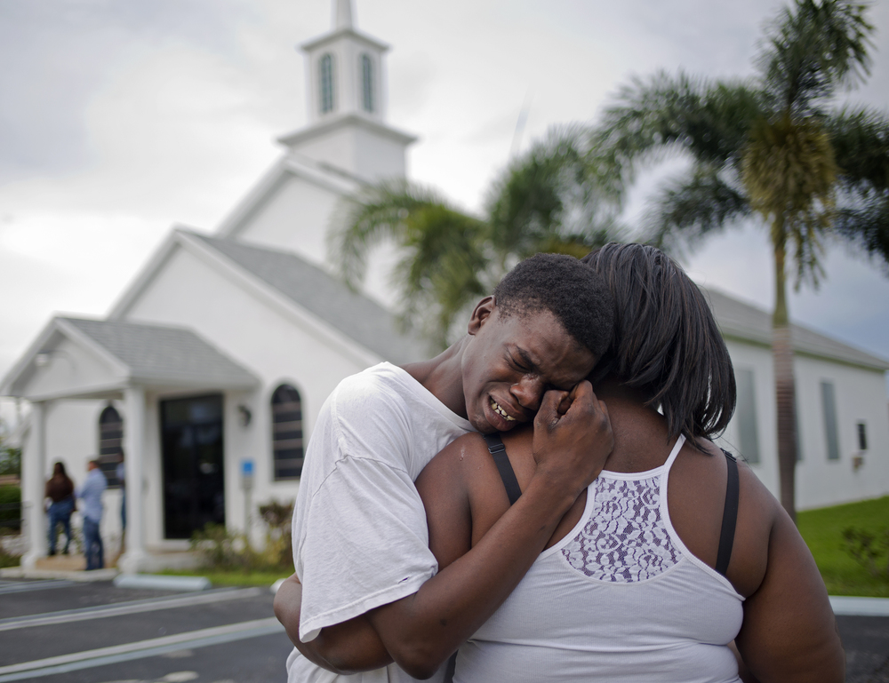 Lawrence Alston, 17, cries on the shoulder of a friend at the wake of his best friend  Johnny Taylor Davis Jr., who was killed in a drive-by shooting in his West Palm Beach neighborhood.     The neighborhood, that is just a few miles away from President Donald Trump's Palm Beach estate, was ravaged by gun violence over the Summer of 2015. T en people were killed and 28 people were wounded.