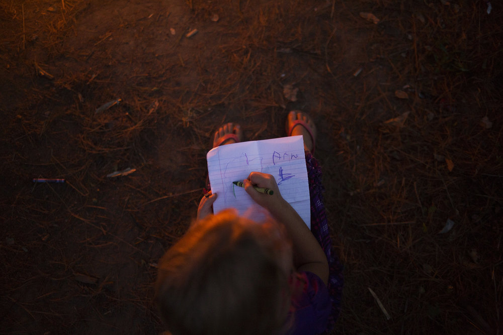 Arianna writes her name and doodles on a piece of paper by the fire as night falls at the camp. She was supposed to be starting kindergarten in a few days, but without an address, they couldn't register her in a school.