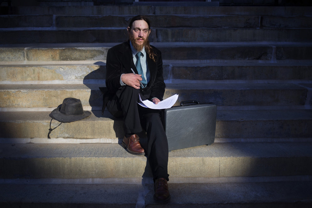 Matt Coffey poses for a portrait on the steps of a church in downtown Portland, Maine. Coffey, who has been homeless over five years, ran for Portland City Council for the second time in 2016.
