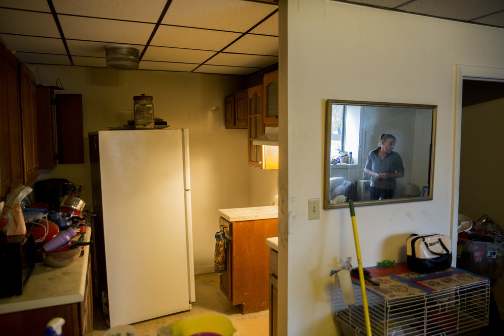 "Chrissy is reflected in the mirror at their apartment a day after a faulty crockpot started a fire in their kitchen. Chrissy put out the fire herself after calling 911 and had to be treated for smoke inhalation. ""I wasn't going to let this place burn."" Chrissy said."