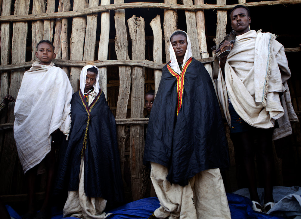 Yemikur, 9, (left center) and Tigiste, 12, (right center) pose for a portrait with their husbands as a young girl from the village peers out from the building behind them. The two girls married brothers in a ten-day wedding ceremony in the Amhara region of Ethiopia.  Child marriage is still prevalent in the rural areas of the country. Two of every five girls in Ethiopia will marry before they are 18 years old.