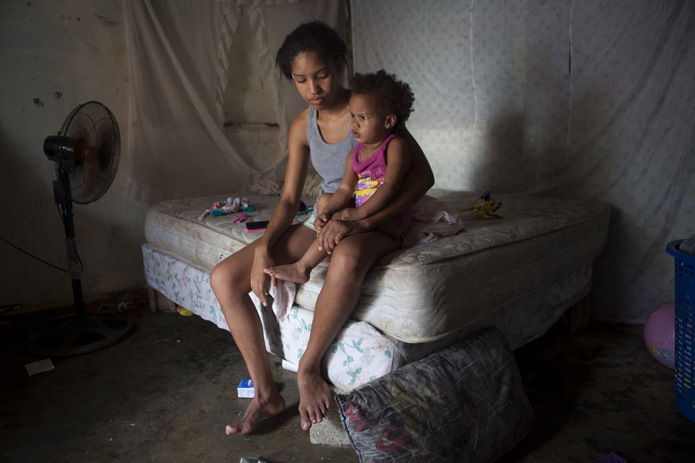 Chabeli sits on her bed with her daughter Isabel. When Chabeli became pregnant at 13 her parents kicked her out of the house. She moved in with Isabel's father, but he was a drug addict and one day he beat her, so she left him. With no one to help her support her daughter, she turned to sex work. Now, she rents one room that has a bed in it for about $45 a month, but she is saving up to build a small house next door to Berenise.