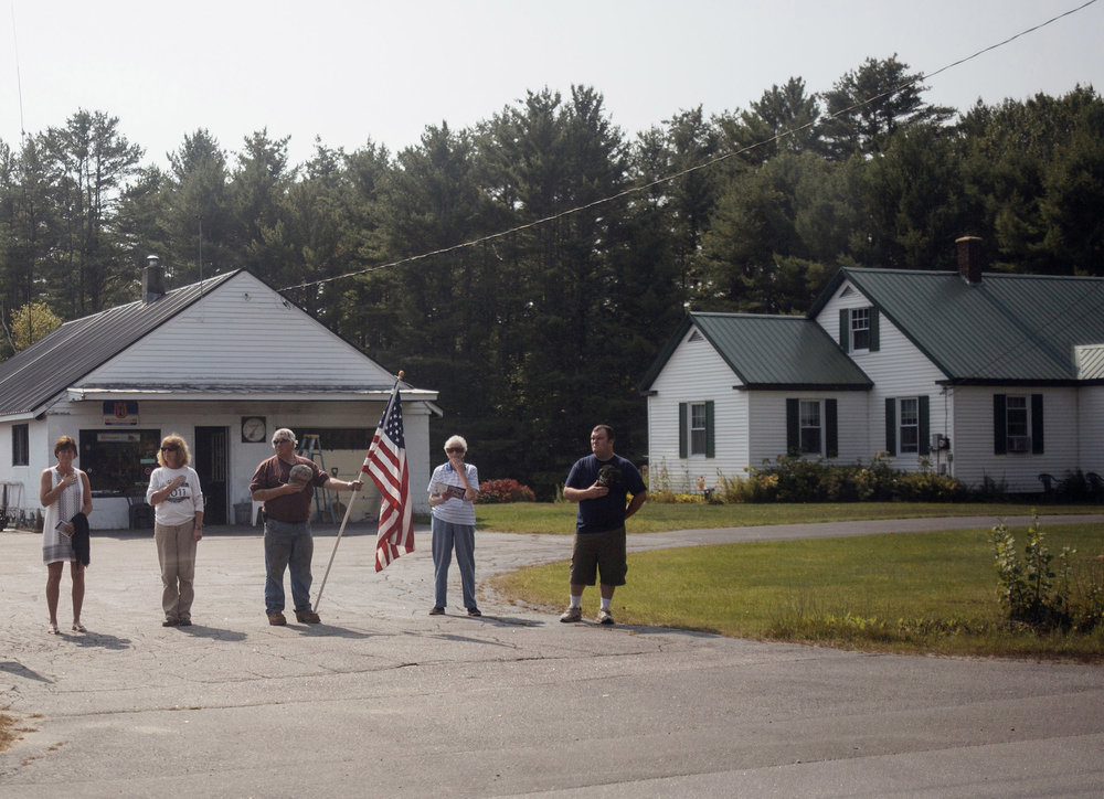 Community members stand alongside the road to pay their respects as Capt. Ben Cross' funeral procession makes its way to Riverside Cemetery in Bethel, Maine. Cross, a 26-year-old Bethel native, was among three Marines killed in August when their MV-22 Osprey crashed into the Coral Sea. His body came home over a month later and hundreds of community members came out to honor him.