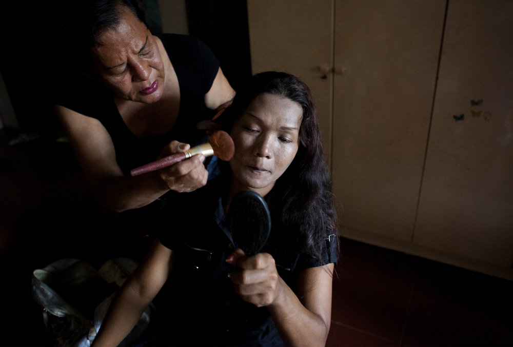 Mumun, who lives full-time at the safehouse for warias, helps a young waria named Intan put on make-up. Mumun worked as a sex worker when she was young and then when she got older became a cosmetologist. Intan is currently making her living as a sex worker.