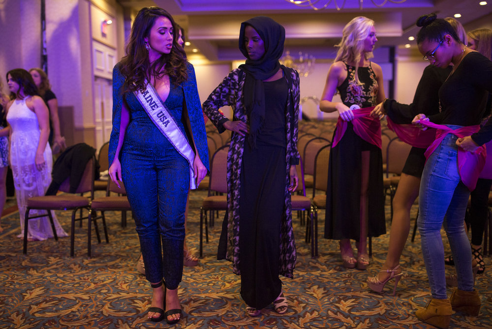 From left, Brooke Harris, Miss Maine USA 2017, helps Ahmed practice her poses before the first night of the Miss Maine USA pageant. Ahmed had never competed in a pageant before being selected for Miss Maine USA and many of her fellow contestants helped her learn the poses.