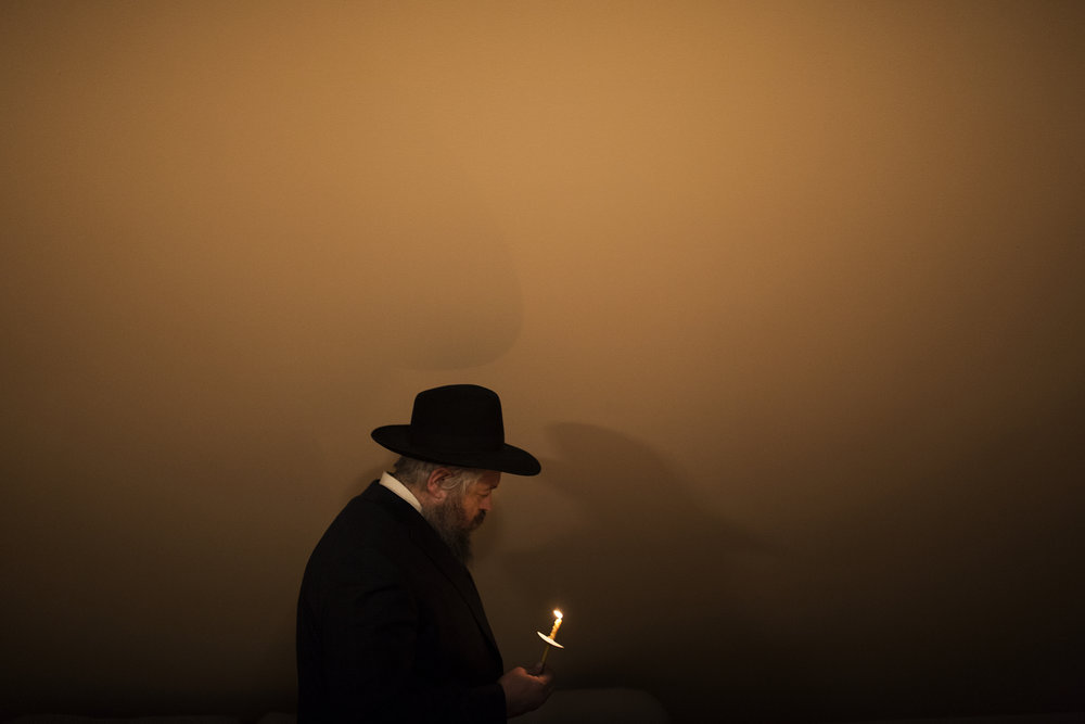 Rabbi Moshe Wilansky leads his family on the search for chametz in their home on the night before the start of Passover in Portland, Maine.