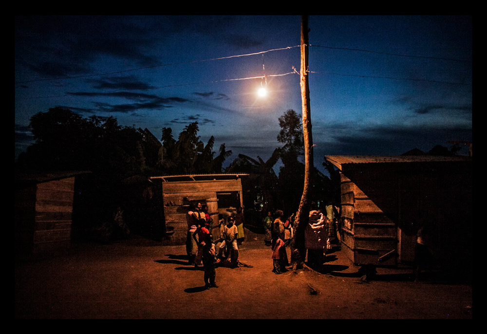 Women and children line up at a grinding mill at dusk