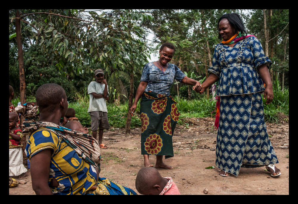 Activist Kahindo Siherya Alphonsine jokes with a Pygmy woman in the village of Upende