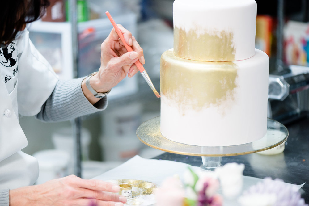 Gia McCollister of Gia's Cakes paints our cake in gold