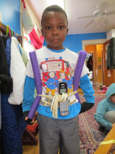 A 5-year old uses a ribbon to hold his superhero gear.