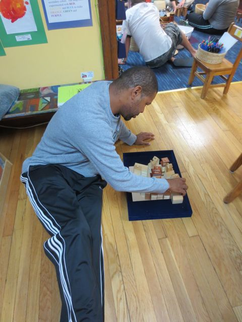 A parent plays with blocks.