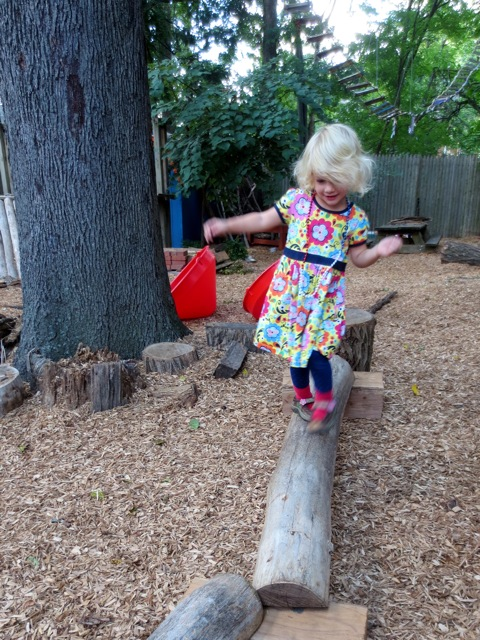 Captured in a moment of grace. She will try this balance thing out. The logs are shifting beneath her feet. She can only walk one or two steps before falling, but she gets right back up. She is simply going to do it, she will walk to the end!