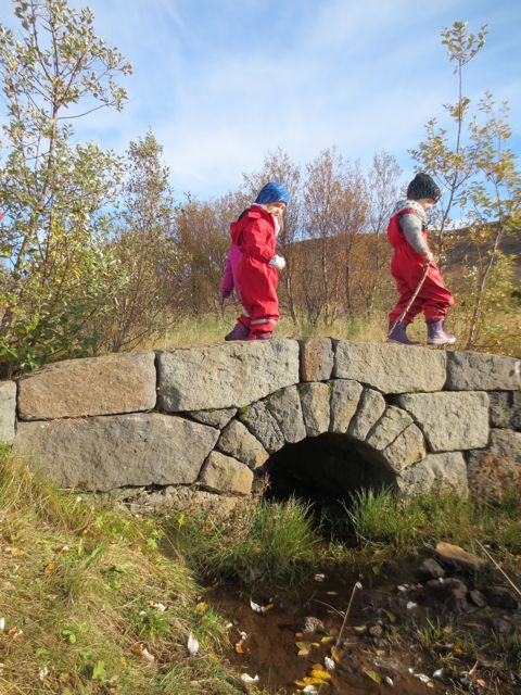 The children cross one of two stone bridges at Stekkjarás.