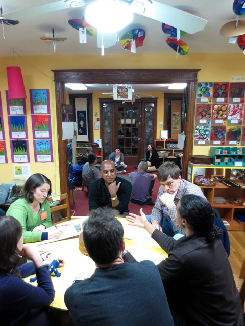 Parents share experiences in small groups during a parent meeting.