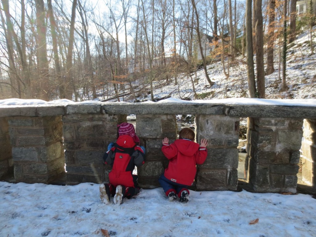 Children stop and look through the pillars of the stone bridge.