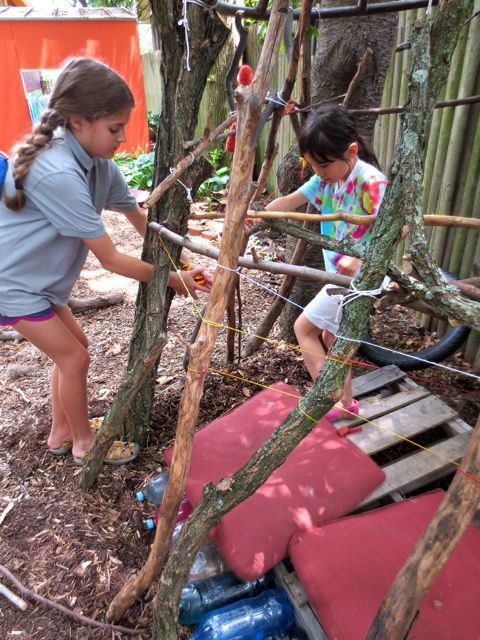 The yarn and ribbon weaving begins. These two started the weaving and then stepped away as others learned the craft of den weaving.