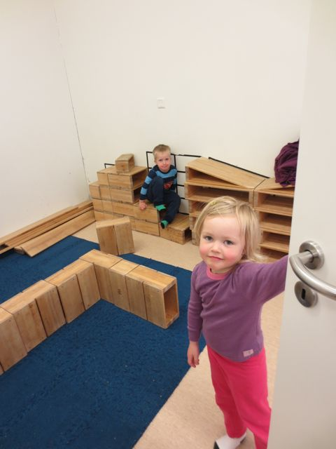 A child opens the door to reveal the structure they are building.
