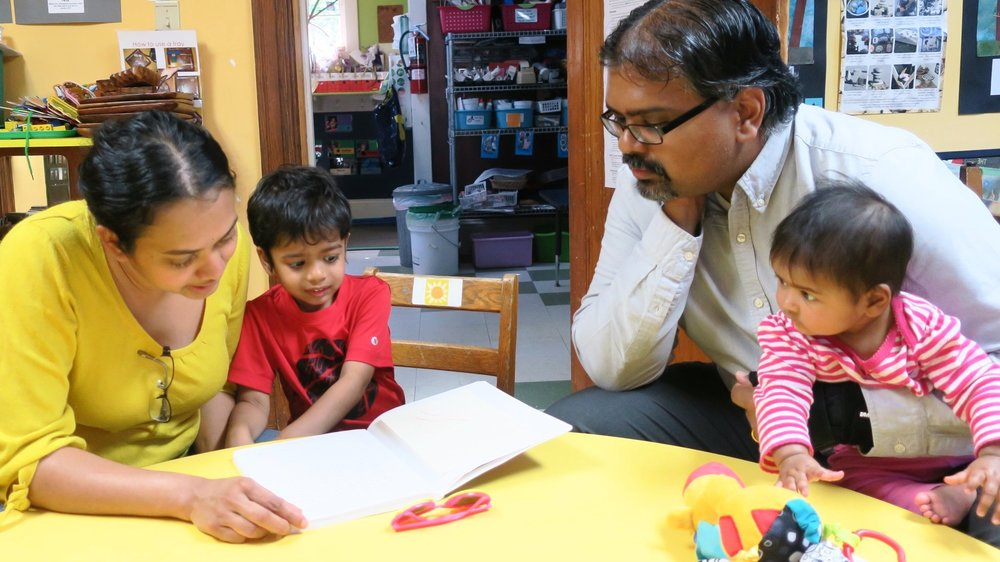 Parents review their child's journal, artwork, and portfolio. There are many check-ins, from weekly class updates, weekly co-oping, and parent trainings, to portfolio conferences led by the children.