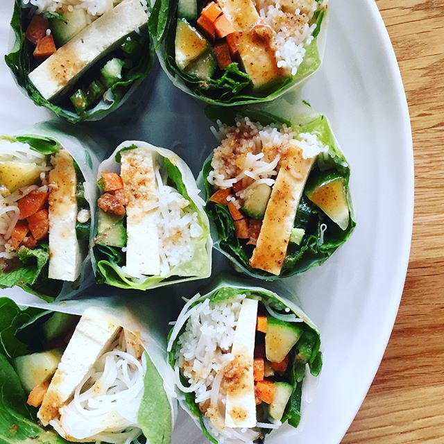 Turns out you can make friends with salad...rolls // these salad rolls are vegan, gluten-free and oh so yummy. The prep is the hardest part so I recommend cleaning and chopping lots of veggies at once so you have them on hand when you get the craving for more, because trust me, you will. 👇🏽 the how to  For the wraps you will need:  rice paper wraps vermicelli noodles all the stuffing: romaine lettuce, cucumbers, carrots, avocado, tofu, jalapeños, basil, mint...anything you like. Slice your veg into long strips and douse them in tamari while you prepare the other ingredients.  For the dressing whisk all the below ingredients together in a bowl. I eyeballed this so taste as you go (this is enough for one person)  1-2T almond butter 2T tamari or low-sodium soy sauce 1t minced ginger 1T maple syrup  squeeze of lime 1t sesame oil (optional) 1T water to thin it out (optional)  Cook your vermicelli noodles by boiling them in water for 3 minutes, rinse in cold water, drain and pat dry. Prepare very warm water in a large bowl and dip a rice wrap in it until it's softened and place on a cutting board wiping off excess water. You don't need to dip it long as that can make it harder to work with, it will continue to absorb water while you work. Top with romaine lettuce first (it keeps all the ingredients in), then your noodles and veg, wrap tightly, tucking the bottom of the wrap in like a burrito. Enjoy with your almond butter dip #healthfoodsnob