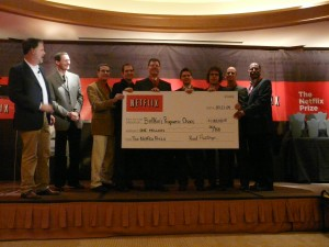 BellKor's Pragmatic Chaos, winners of the Netflix Prize, display their million-dollar check (Image Credit: Eliot Van Buskirk/Wired.com).
