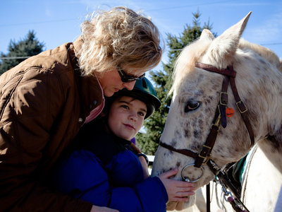 Cathy Coleman is a speech pathologist for the Northern Virginia Therapeutic Riding Program. She uses a horse named Happy in her therapy sessions with 9-year-old Ryan Shank-Rowe, who has autism.   Maggie Starbard/NPR
