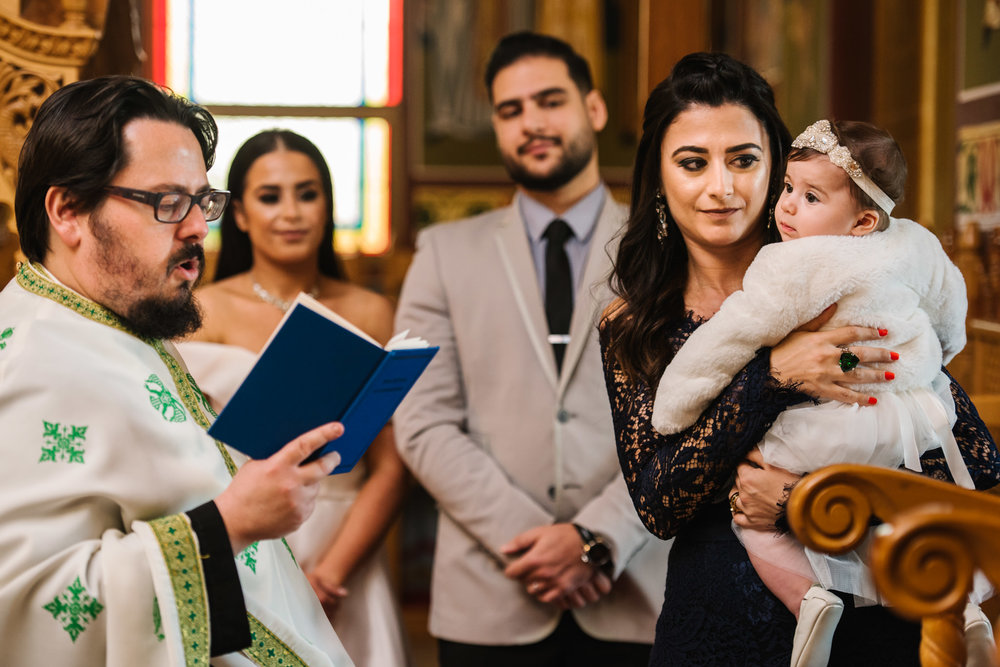 Priest and baby during christening service