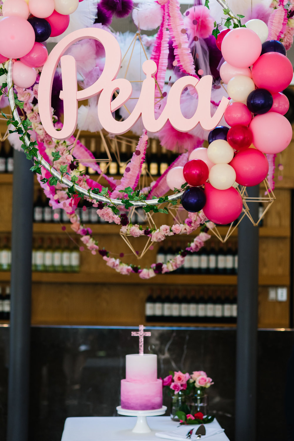 Cake table with balloons and name sign