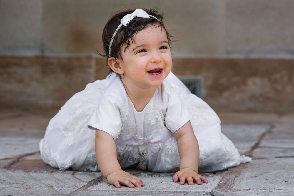 Smiling baby in christening gown at Oatlands House