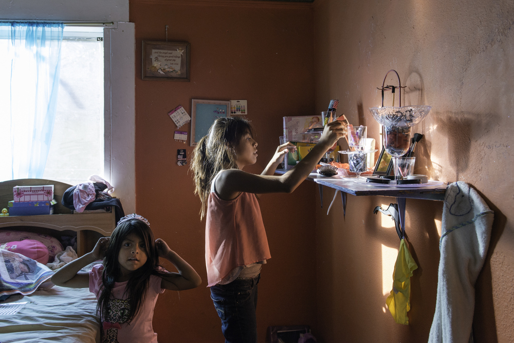 Amada Silva, 12, and Yadira Silva, 6, clean their room after school. The sisters suffer from asthma so their mother makes them clean their room everyday to minimize dust.