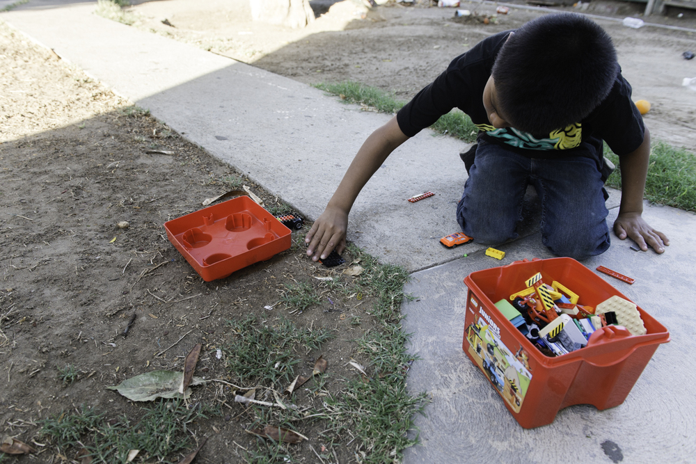 Renato Silva, 10, plays with his toy cars in the backyard of his home. His mother says that the dirt exacerbates his asthma symptoms, but keeping him from playing is a challenge.
