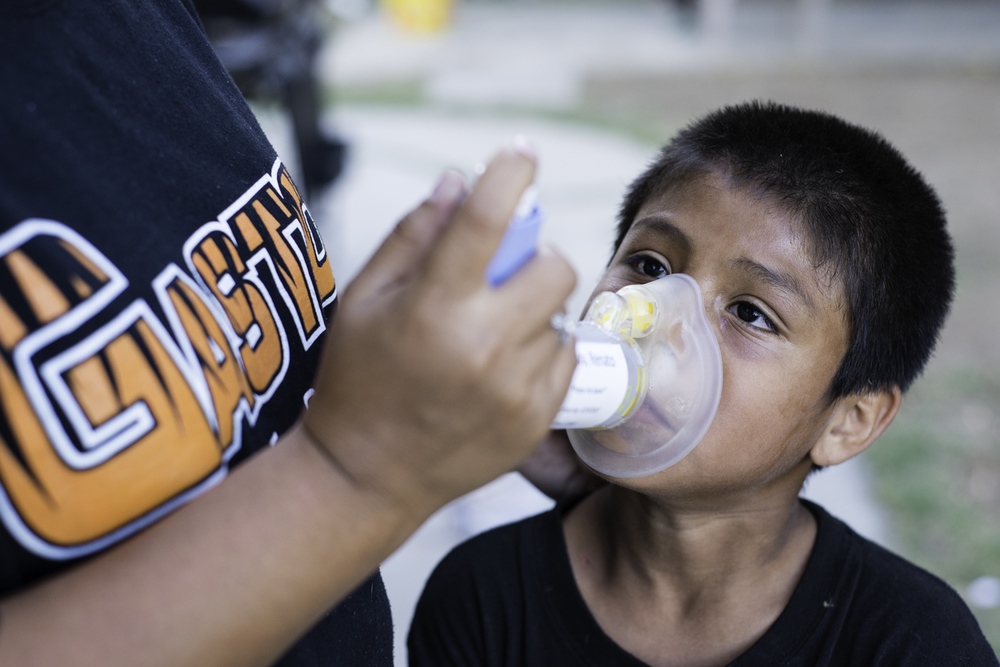 Every evening Dalia Mondragon administers an inhaler to her son, ten-year-old Renato Silva, using a spacer device with a facemask. Out of her four children, his asthma is the worst.