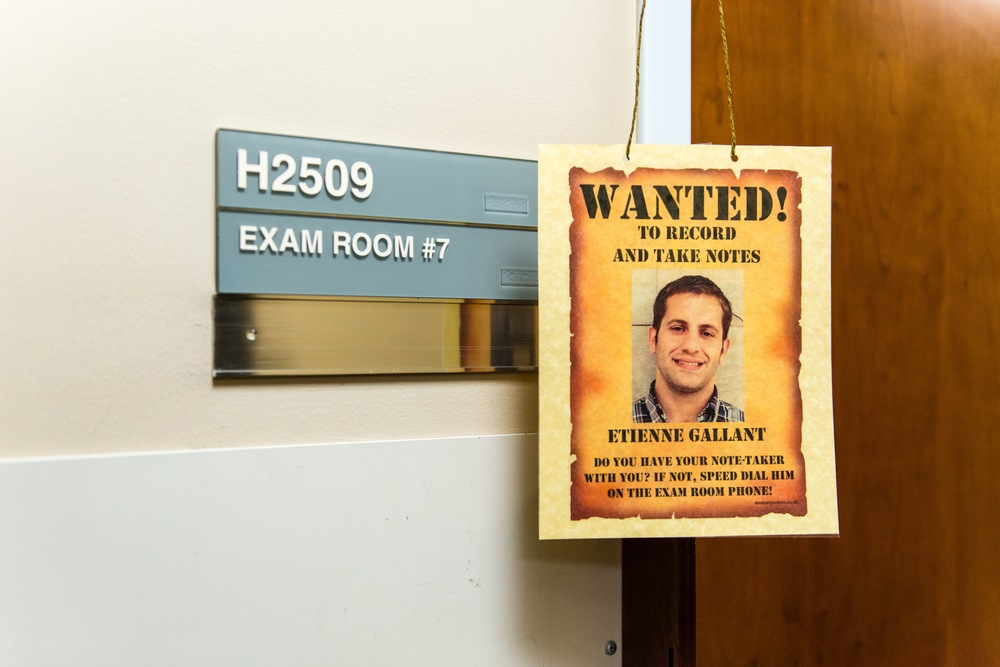 The Patient Support Corps at UC San Francisco Medical Center pairs interns with patients to provide support during visits. A sign with the student's face hangs outside the exam room to remind patients to call their assigned note-taker