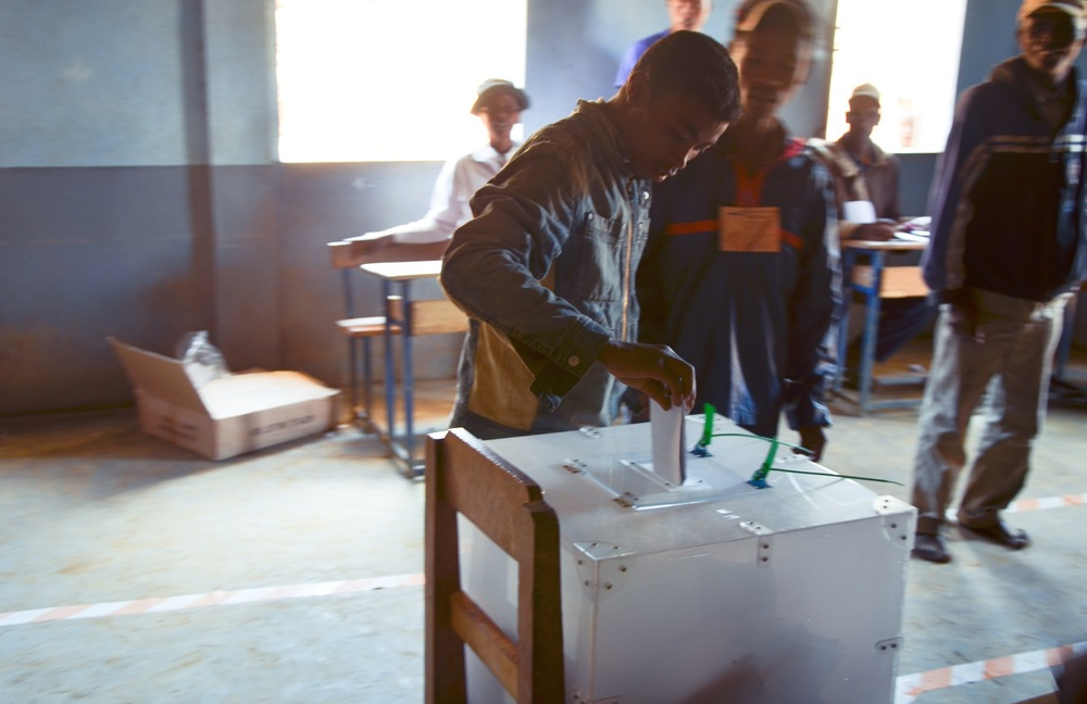 A young man drops his vote in the ballot box. Photo: Alizé Carrère