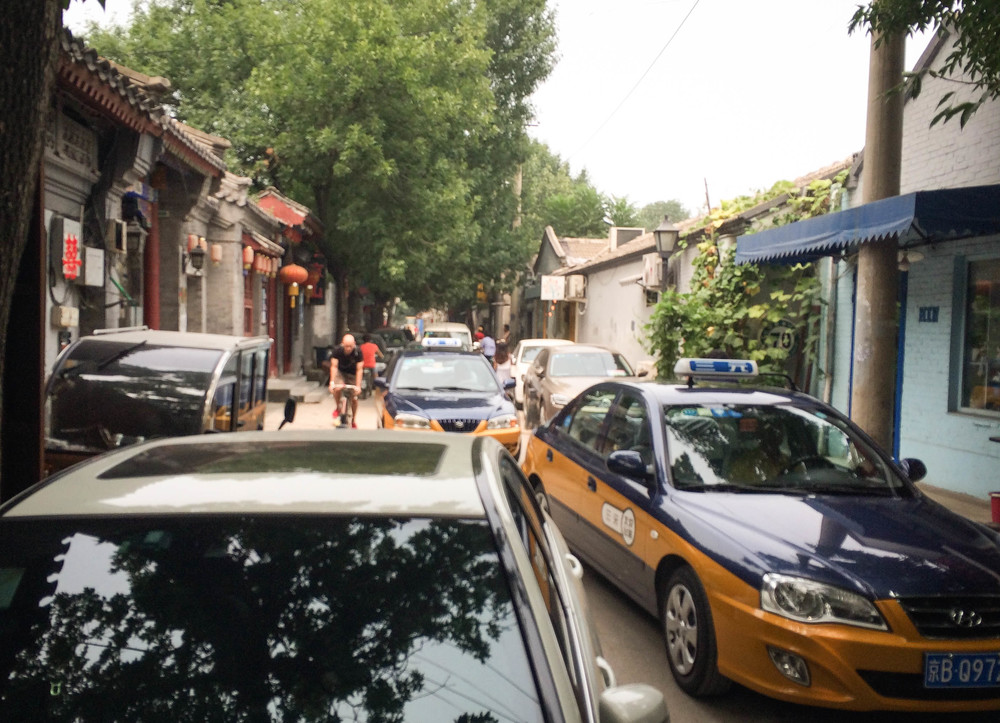 Beijing's small historical streets were never designed to accommodate the influx of cars that now squeeze their way through the car-clogged alleys. (Photo by Alizé Carrère)