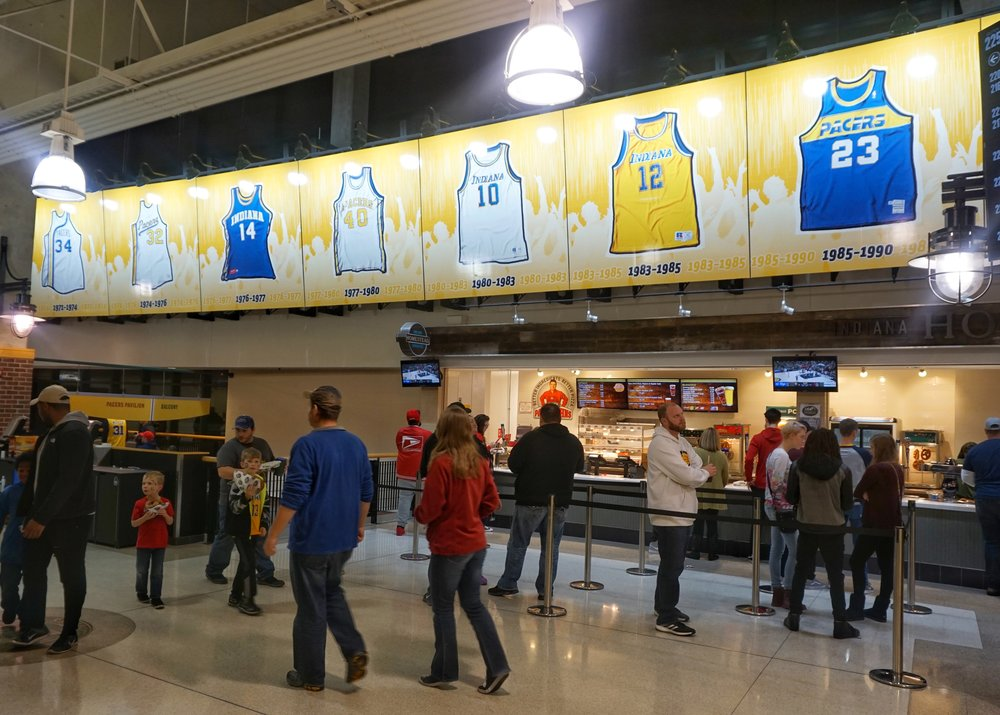 A sign over a concession stand displays the jerseys of prominent players from previous decades.