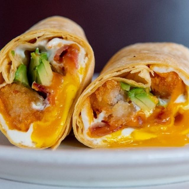 The La Neta breakfast burrito available on @postmates and @ubereats eggs, tater tots, bacon, avocado, cheddar cheese, and crema served with salsa roja on the side. 🍳🥓🧀🥑🌯
