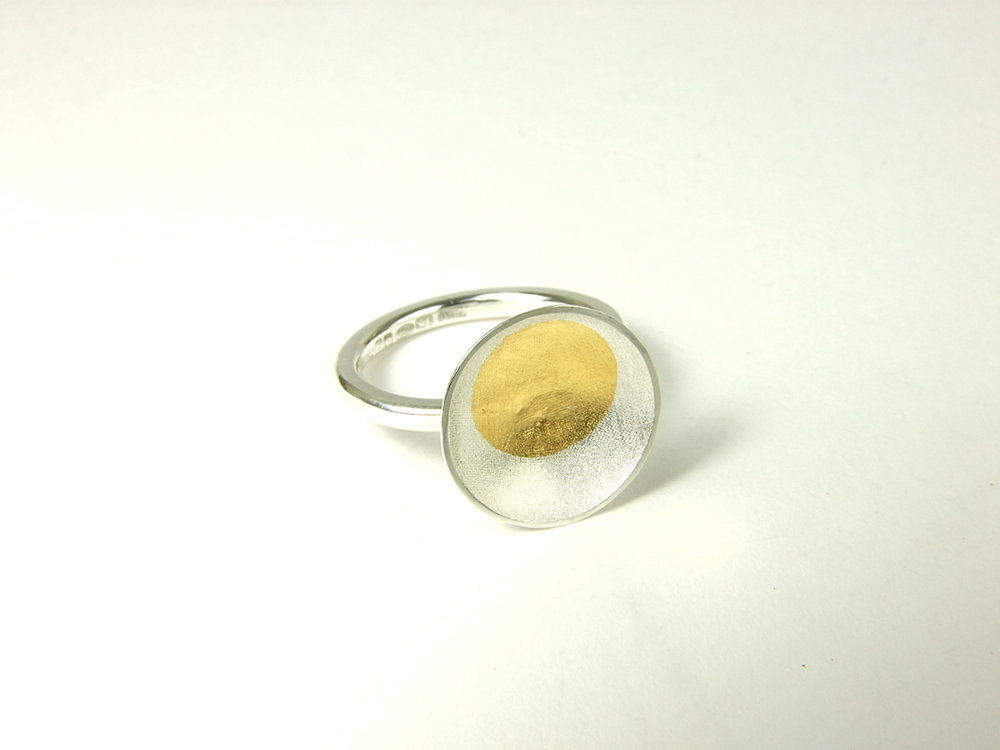 Front view of Argentium silver ring with shallow textured oval with a round Keum-Boo detail in 22 ct yellow gold. (HBM089B)
