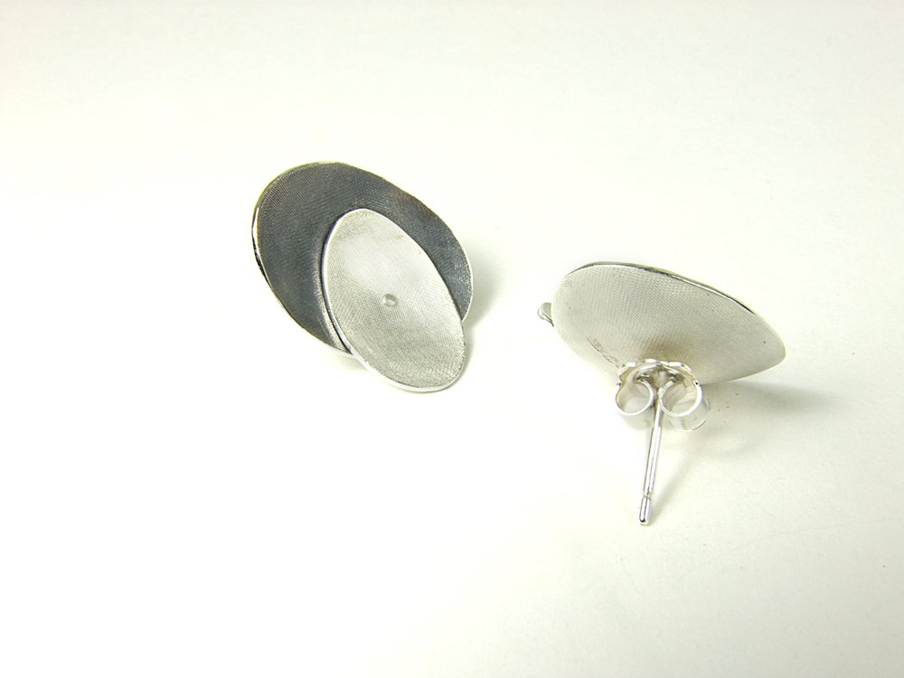 Rear view of large Argentium silver ear studs with two domed oval shapes, partially oxidised. (HBM088A)