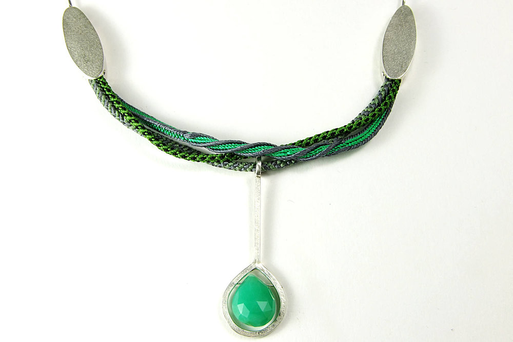 Detailed view of the silk braid and pendant.
