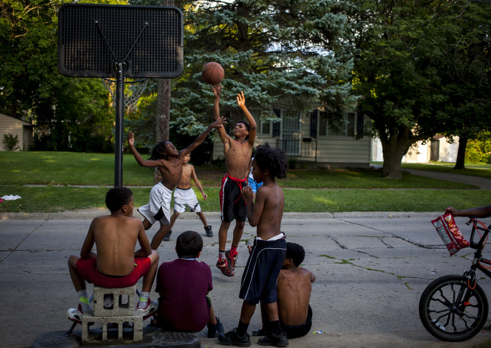 Anthony Richardson, 12, shoots as Boop Hardy, 10, reaches to block him during a game on Saginaw's Westside. Games often start all in the afternoons and continue until dark.