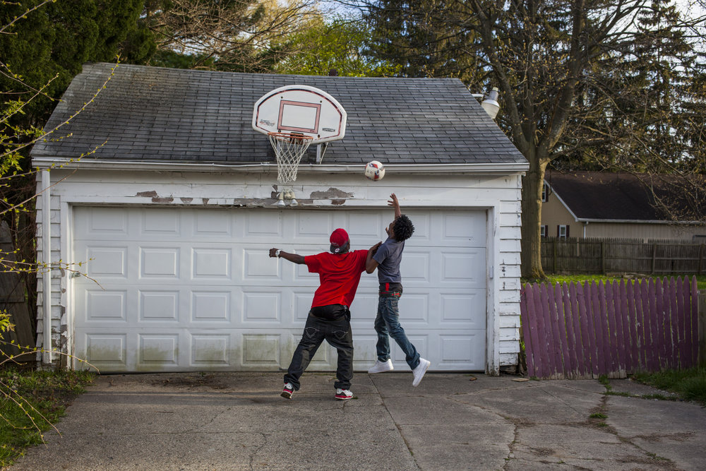 Davion Maxwell, 15, of Saginaw goes up to shoot past his nephew Nico Smith, 18, of Flint in the neighbor's driveway.