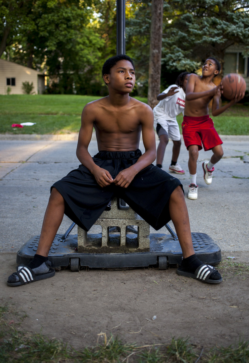 Briyan Nicholson, 11, of Saginaw takes a break from playing while the game continues behind him on Saginaw's Westside.