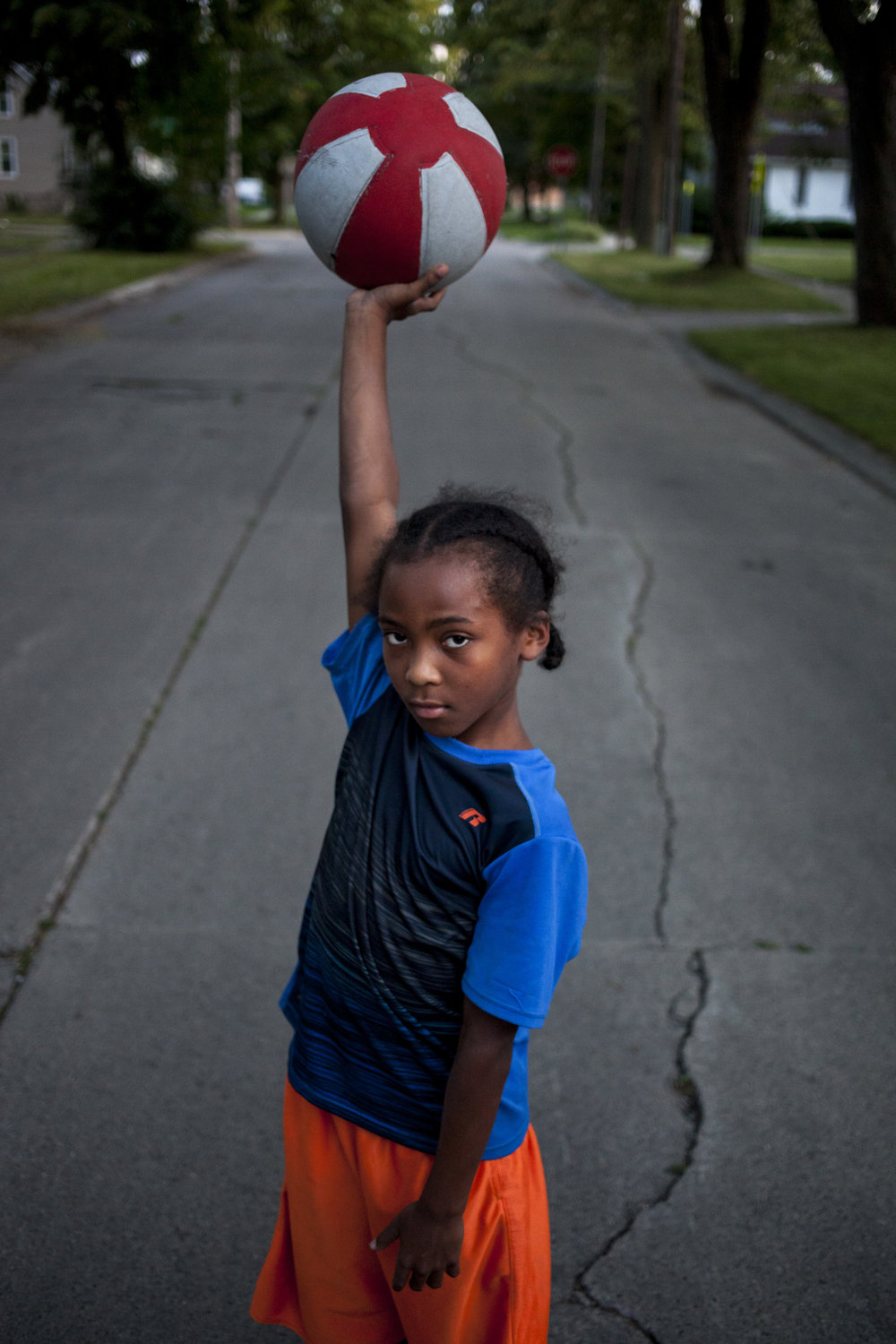 Cameron Nicholson, 9, of Saginaw holds a ball above his head as poses during a break from a game on the Westside of Saginaw.