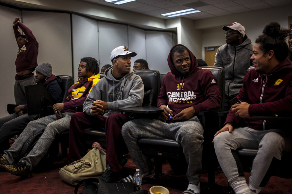 """Before an early morning practice, Ray Golden, Jr., talks with his teammates on the Central Michigan University football team. As a defensive back, Golden takes his responsibility to his team serious and refers to football as his """"job."""" Because of the long hours spent with his team, the football team is a second family for Ray."""