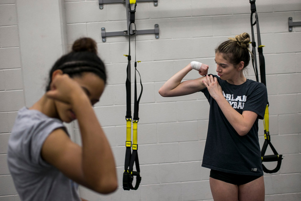 Kiana Fallaha, 15, shows off her biceps during a weight training session at Harlan High School. The team completes early morning weight training sessions twice a week together.
