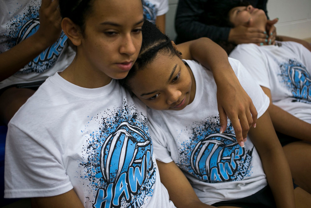 Ashley Chatham, 16, wraps her arm around Jevani Hanspard, 15, as she leans into Chatham as they wait to leave Harlan High School for the team's first game.
